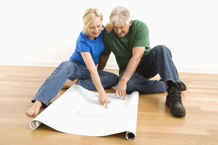 Middle-aged couple sitting on floor looking at and discussing architectural blueprints together. photo