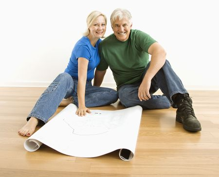 Middle-aged couple sitting on floor with architectural blueprints. Stock Photo
