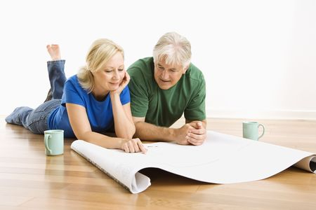 reviewing: Middle-aged couple looking at architectural blueprints together.