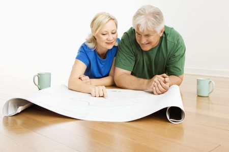 Middle-aged couple lying on floor looking at and discussing architectural blueprints together. photo