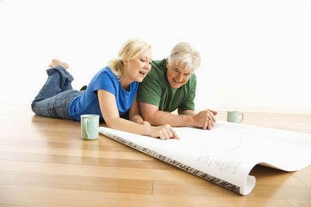 two floors: Middle-aged couple lying on floor looking at and discussing architectural blueprints together.