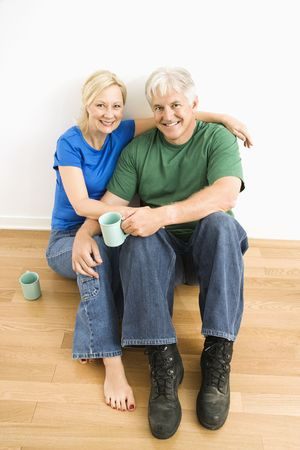 Middle-aged couple sitting on floor together drinking coffee. photo
