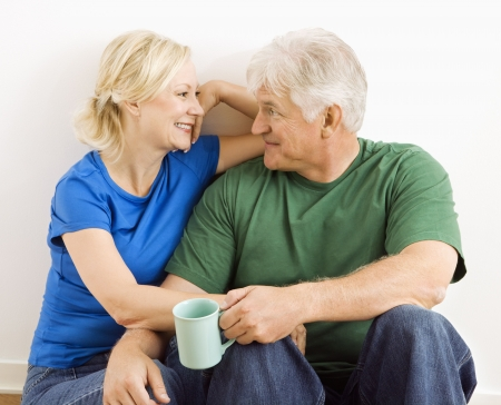 two people talking: Middle-aged couple sitting together snuggling and drinking coffee. Stock Photo