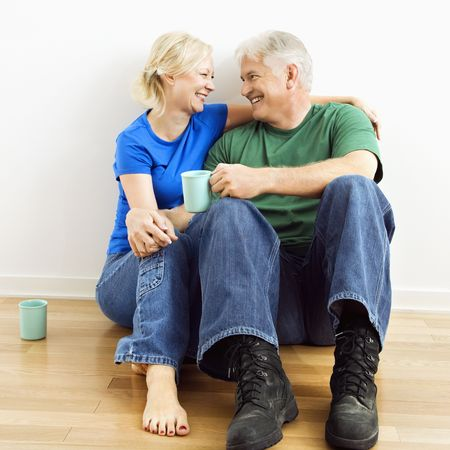 Middle-aged couple sitting on floor snuggling and drinking coffee. Reklamní fotografie - 3557494
