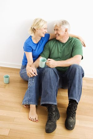 snuggling: Middle-aged couple sitting on floor snuggling and drinking coffee.