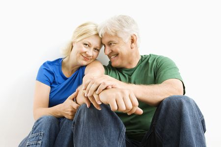 Middle-aged couple sitting together smiling. Stock Photo - 3557469