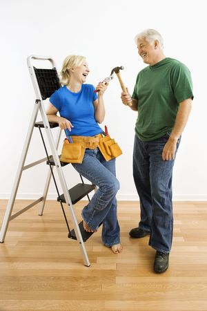 Middle-aged couple with household tools next to ladder. photo