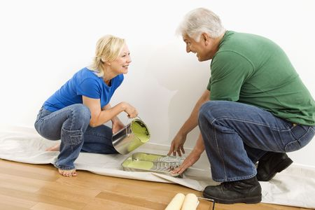 Middle-aged couple pouring paint into tray on drop cloth. Stock Photo - 3557505