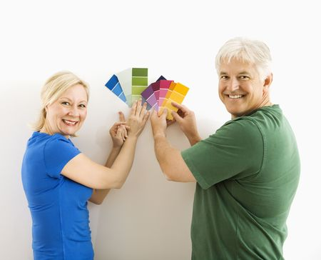 Middle-aged couple holding up and comparing paint swatches. photo