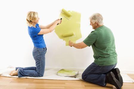 Middle-aged couple beginning to paint wall green over drop cloth. photo