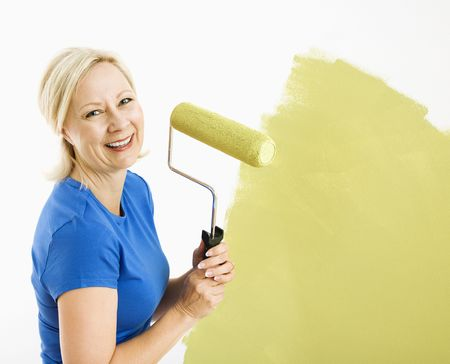 Middle-aged woman painting wall green with paint roller smiling at viewer. photo