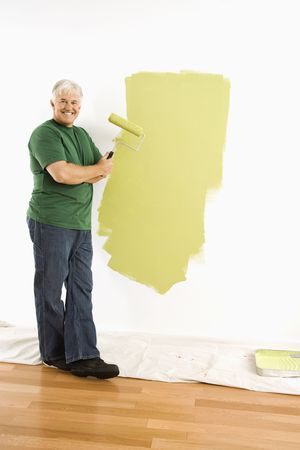 Middle-aged man painting wall green with paint roller smiling at viewer. Stock Photo - 3557405