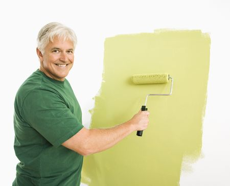 Middle-aged man painting wall green with paint roller smiling at viewer. Stock Photo - 3557467