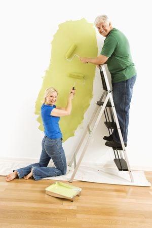 Middle-aged couple painting wall green and looking at viewer. Stock Photo - 3557428