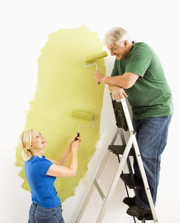 Middle-aged couple painting wall green with male on ladder. photo