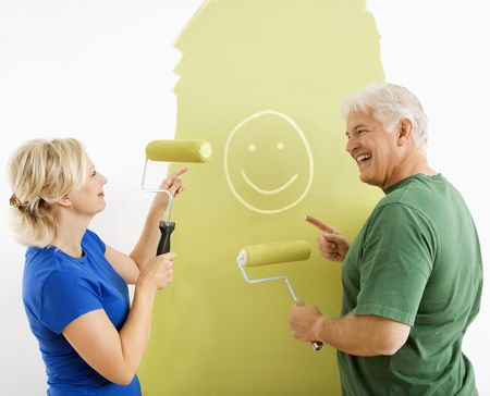 Middle-aged couple painting wall green finger-painting smiley face for fun. photo