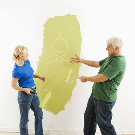Middle-aged couple painting wall green finger-painting smiley face figurine for fun. Stock Photo - 3557403