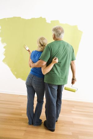 Middle-aged couple painting wall green observing their work. photo