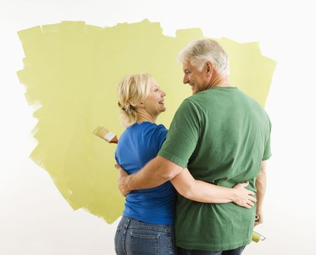 Middle-aged couple painting wall green observing and discussing their work. photo