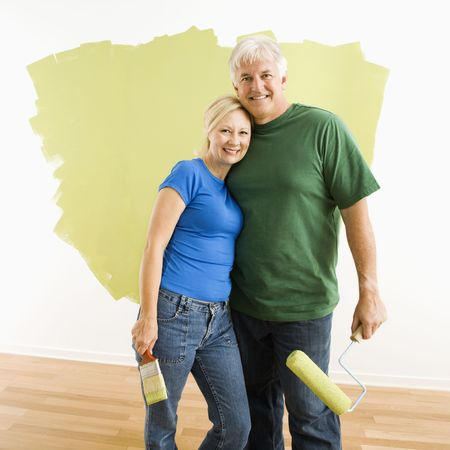 Middle-aged couple in front of wall they are painting green. photo