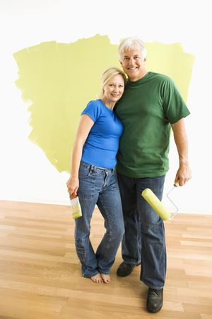 Middle-aged couple in front of wall they are painting green. Stock Photo - 3557464