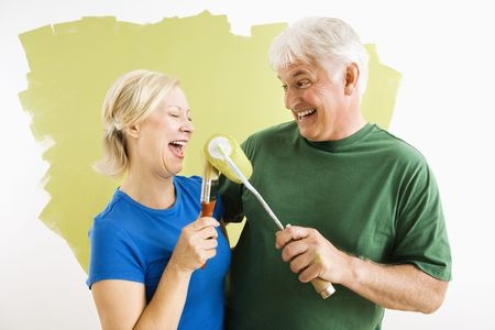Middle-aged couple painting wall green playing with paint utensils. photo