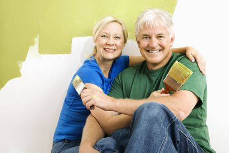 Middle-aged couple snuggling in front of wall they are painting green. Stock Photo - 3557507