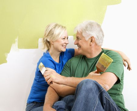 Middle-aged couple snuggling in front of wall they are painting green. photo