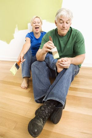Middle-aged couple in front of wall they are painting green while male tries to paint womens toenails with paintbrush. photo