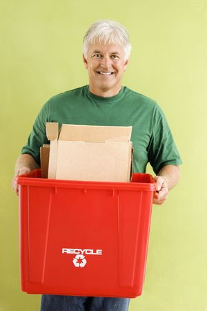 Portrait of smiling adult man holding recycling bin full of cardboard. Stock Photo - 3557476