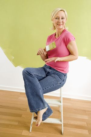 Portrait of smiling adult woman sitting in front of half-painted wall with paintbrush. Stock Photo - 3557496