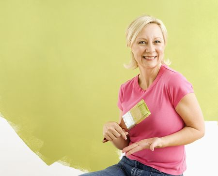 Portrait of smiling adult woman sitting in front of half-painted wall with paintbrush. Stock Photo - 3557440