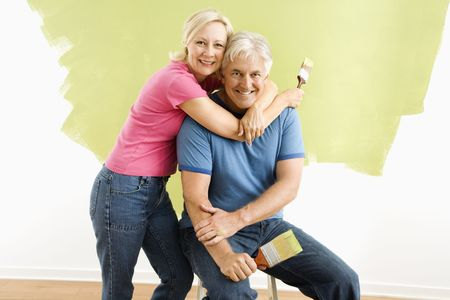 Portrait of smiling adult couple sitting in front of half-painted wall with paintbrushes. Stock Photo - 3557480