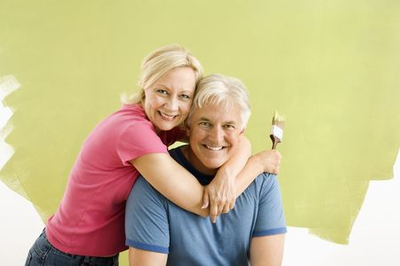 Portrait of smiling adult couple sitting in front of half-painted wall with paintbrushes. photo