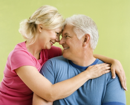 Portrait of smiling middle-aged couple in front of green wall snuggling. Stock Photo - 3557517