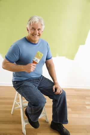 Portrait of smiling adult man sitting in front of half-painted wall with paintbrush. photo