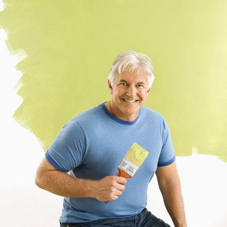Portrait of smiling adult man sitting in front of half-painted wall with paintbrush. Stock Photo - 3557426