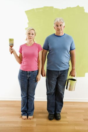 Portrait of unhappy adult couple standing in front of half-painted wall with paint supplies \