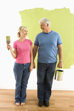 Portrait of happy adult couple standing in front of half-painted wall with paint supplies Stock Photo - 3557493