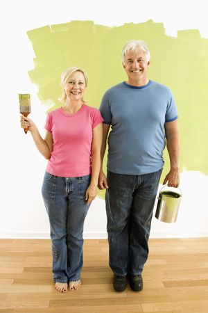 Portrait of happy adult couple standing in front of half-painted wall with paint supplies