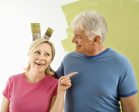 Portrait of happy adult couple standing in front of half-painted wall while man makes bunny ears with paintbrushes behind womans head. photo