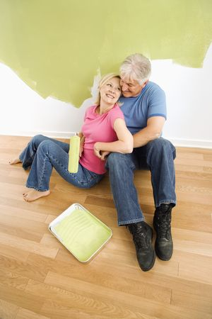 Portrait of happy adult couple sitting in front of half-painted wall with paint supplies snuggling. Stock Photo - 3557513