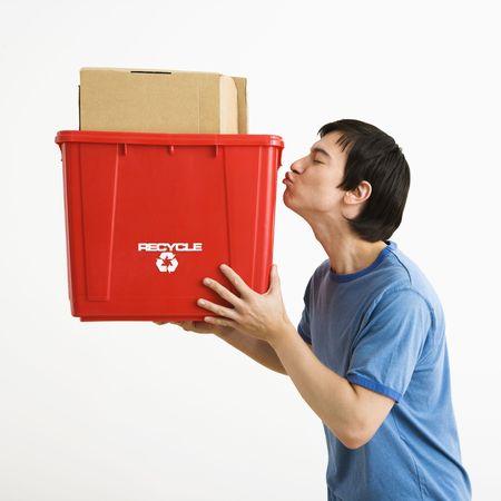 young man standing: Ritratto di giovane uomo asiatico in piedi baciando il riciclaggio bin. Archivio Fotografico