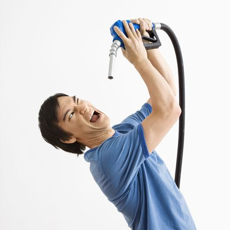 Asian young man fighting with gasoline pump nozzle. Stock Photo