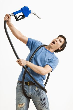 half price: Man fighting with gas pump which has him entangled. Stock Photo