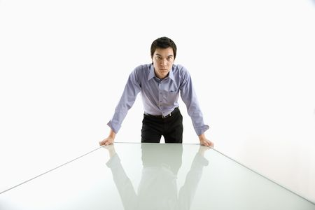 Young Asian business man standing over conference table. photo