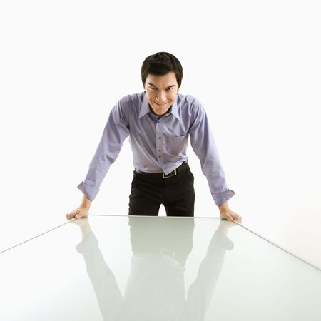 devilish: Young Asian business man standing over conference table with devilish grin.