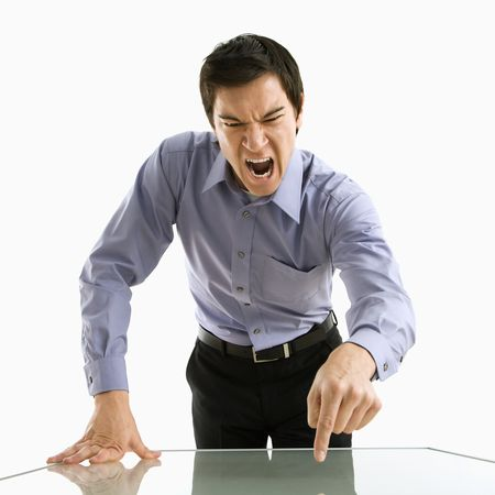 man yelling: Young Asian business man standing yelling at unseen person. Stock Photo