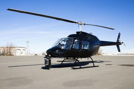 mounted: Zwarte helikopter met camera gemonteerd op voorzijde geparkeerd op luchthaven geasfalteerd.