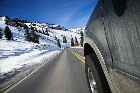 Perspective shot of SUV driving down road in snowy Colorado during winter. photo